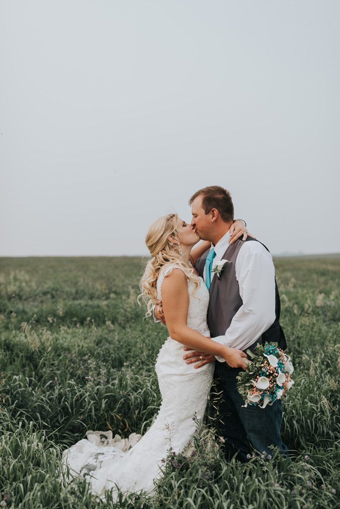 bride and groom kiss holding bouquet family farm cypress county