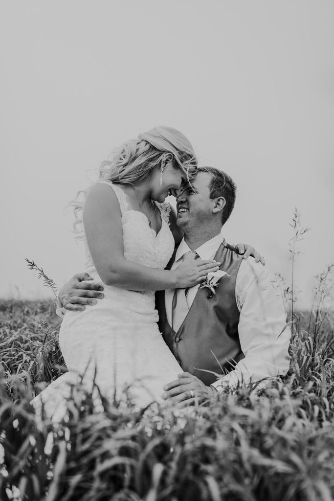 bride sits on grooms lap in tall grass smiling at each other