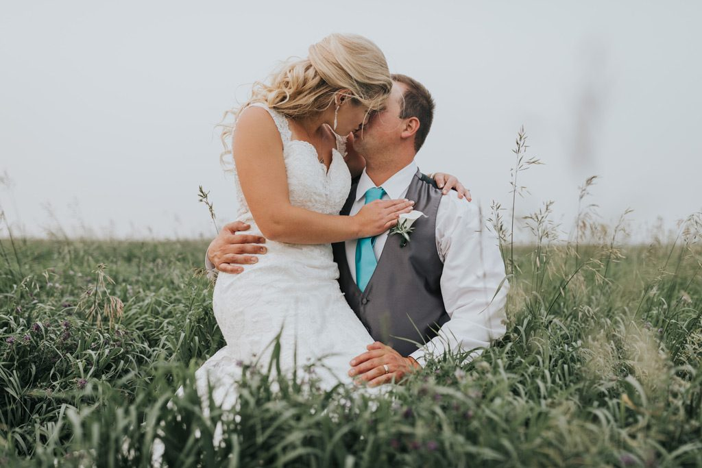 wedding couple kisses while sitting in field of tall grass