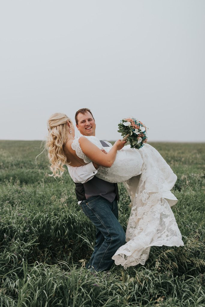 groom carries bride through field smiling