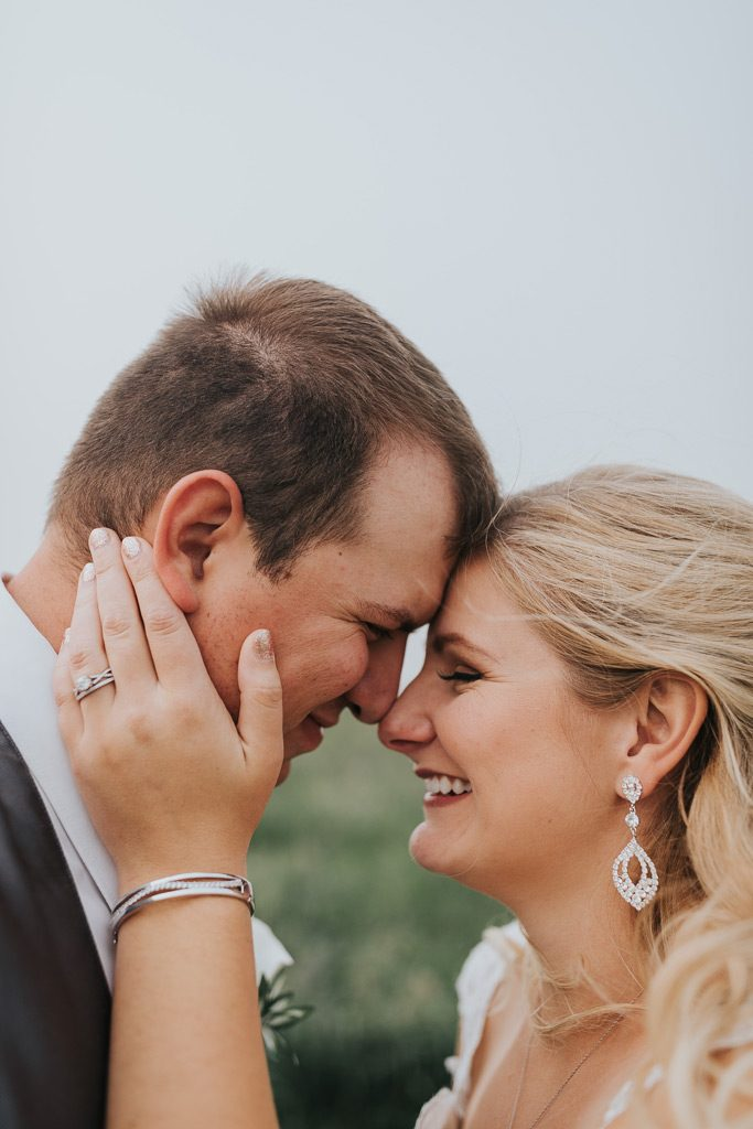 bride pulls groom close to her smiling