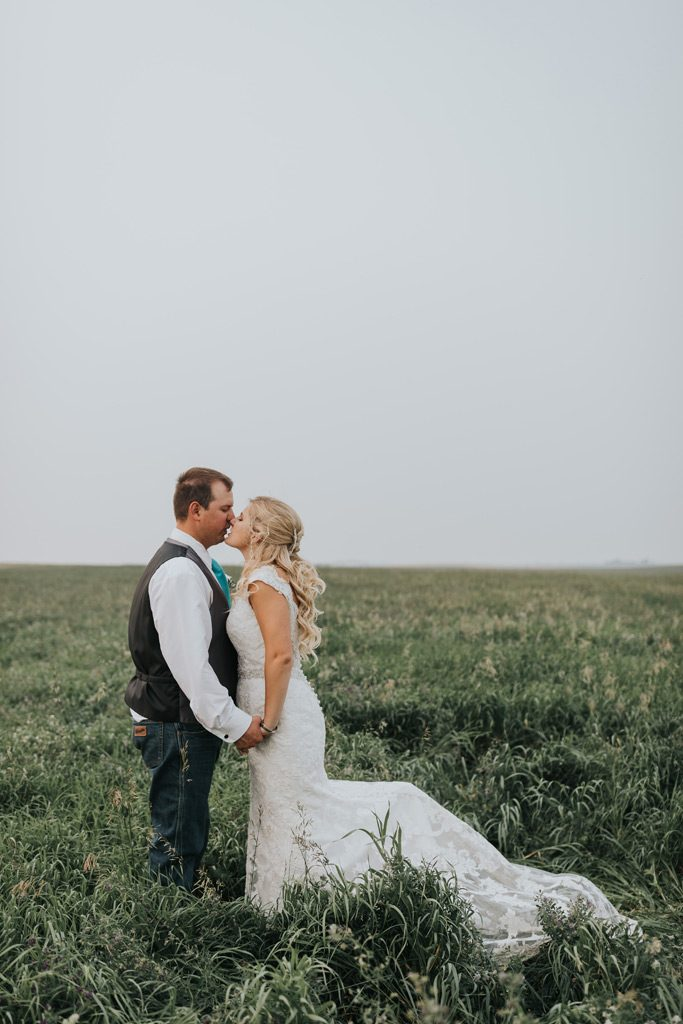 bride and groom kiss in field family farm wedding
