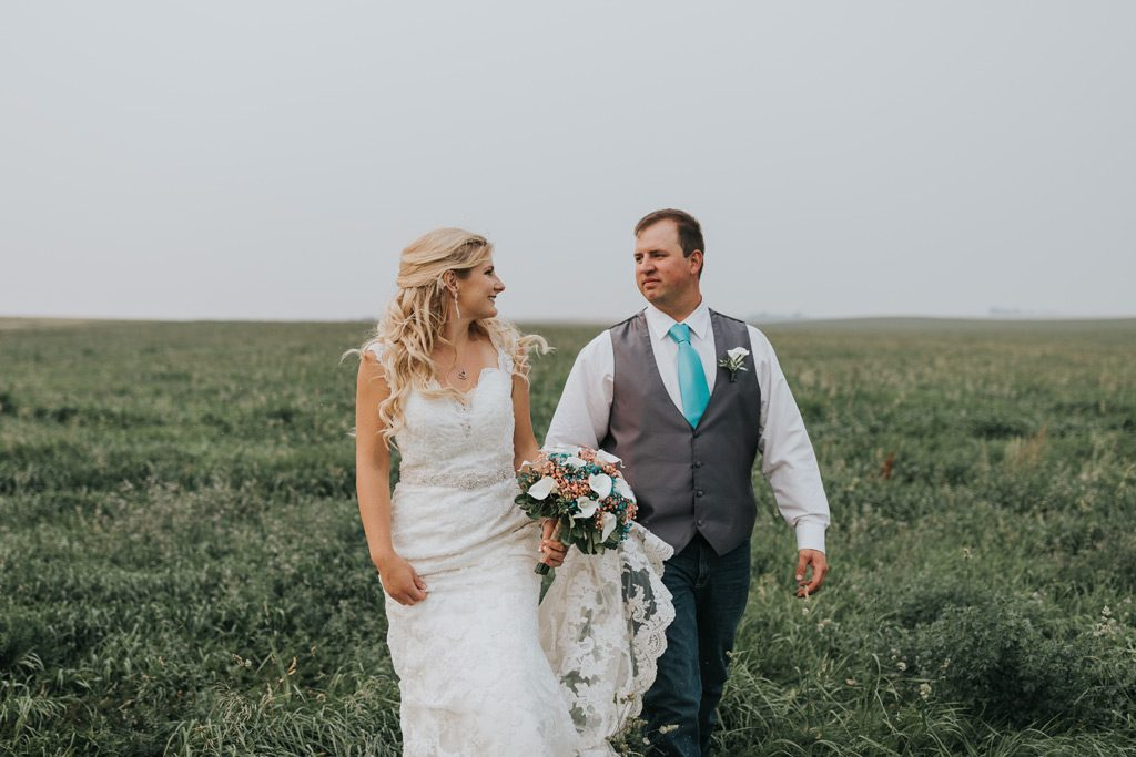 groom carries brides train walking through field