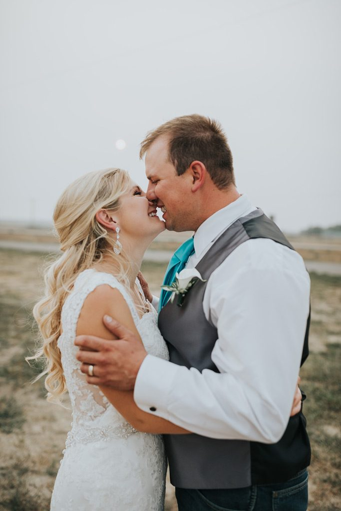 bride and groom smiling before a kiss