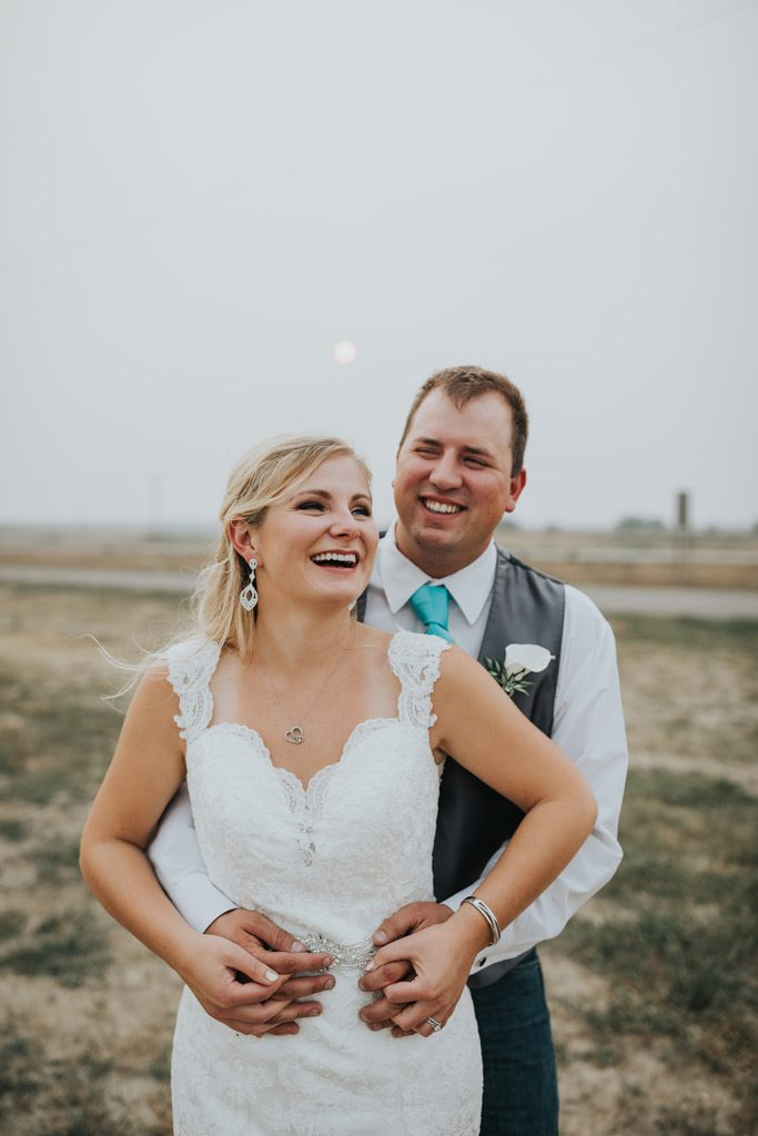 bride and groom laugh while embracing smoky wedding day