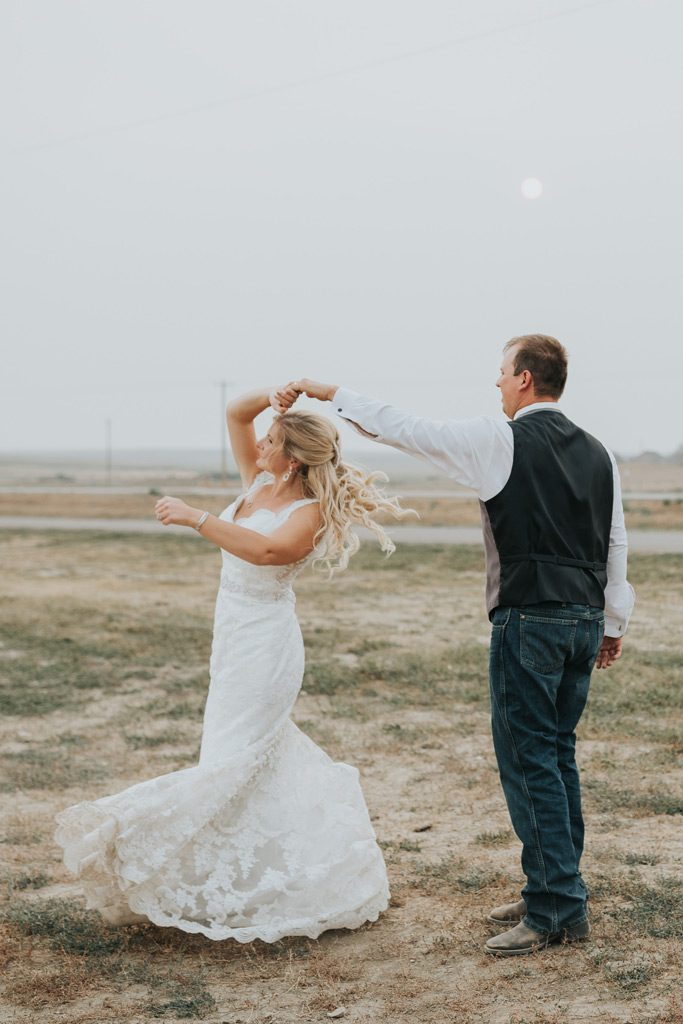 groom twirls bride on hazy wedding day