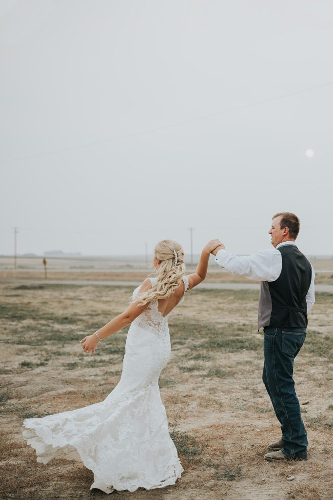 groom dancing with bride spinning on smoky sky wedding day