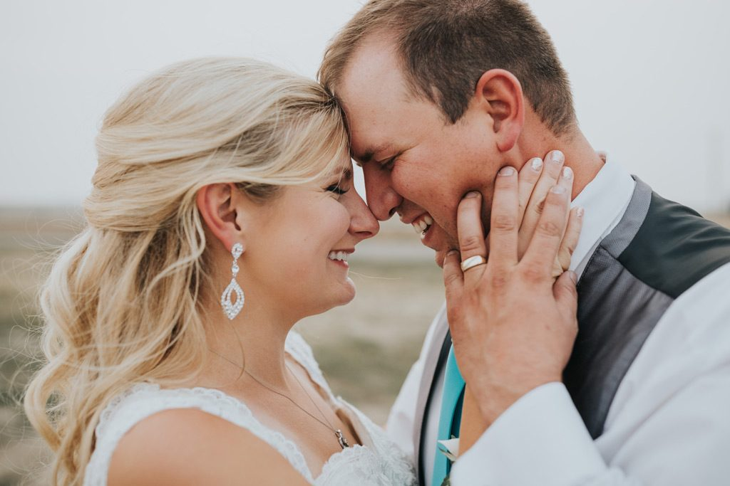 groom holds brides hand on his face foreheads together smiling