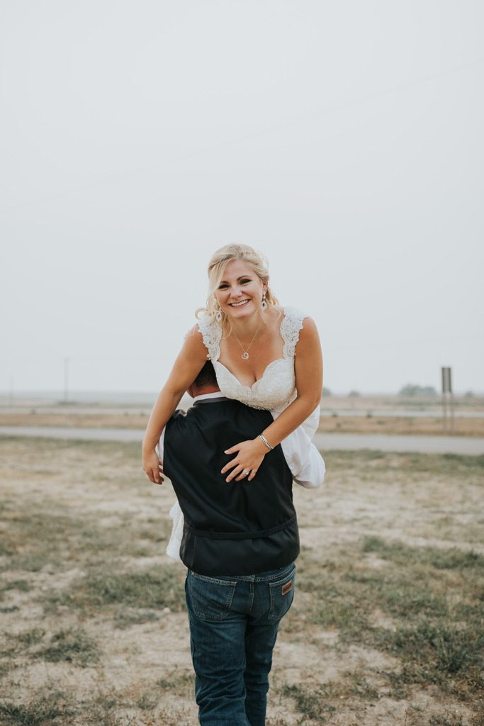 bride smiles as groom carries her away fireman style