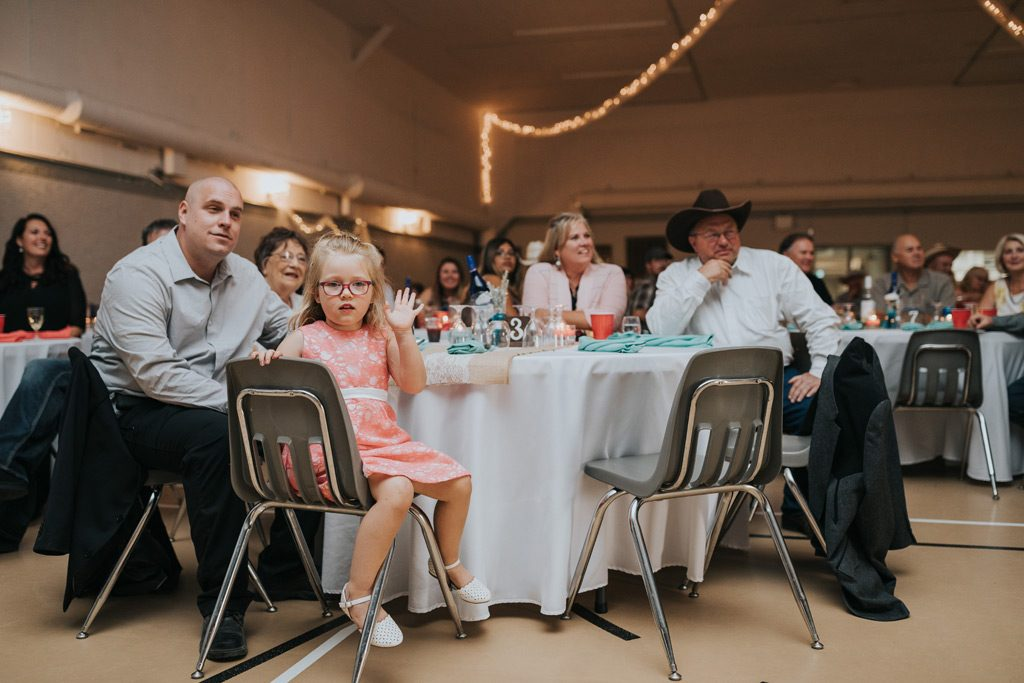 little girl waves to the camera during wedding reception
