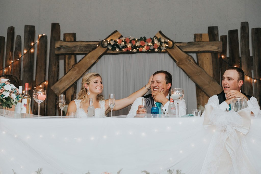 bride and groom laughing during wedding reception speech