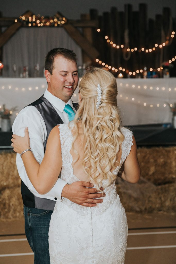 groom smiles at bride during first dance country wedding reception