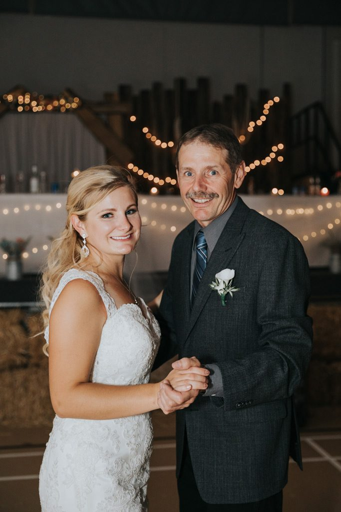 bride dances with dad smiling for camera country reception