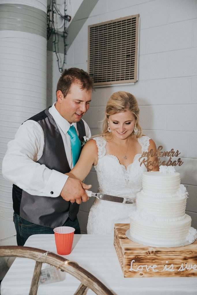 bride and groom smile cutting cake together