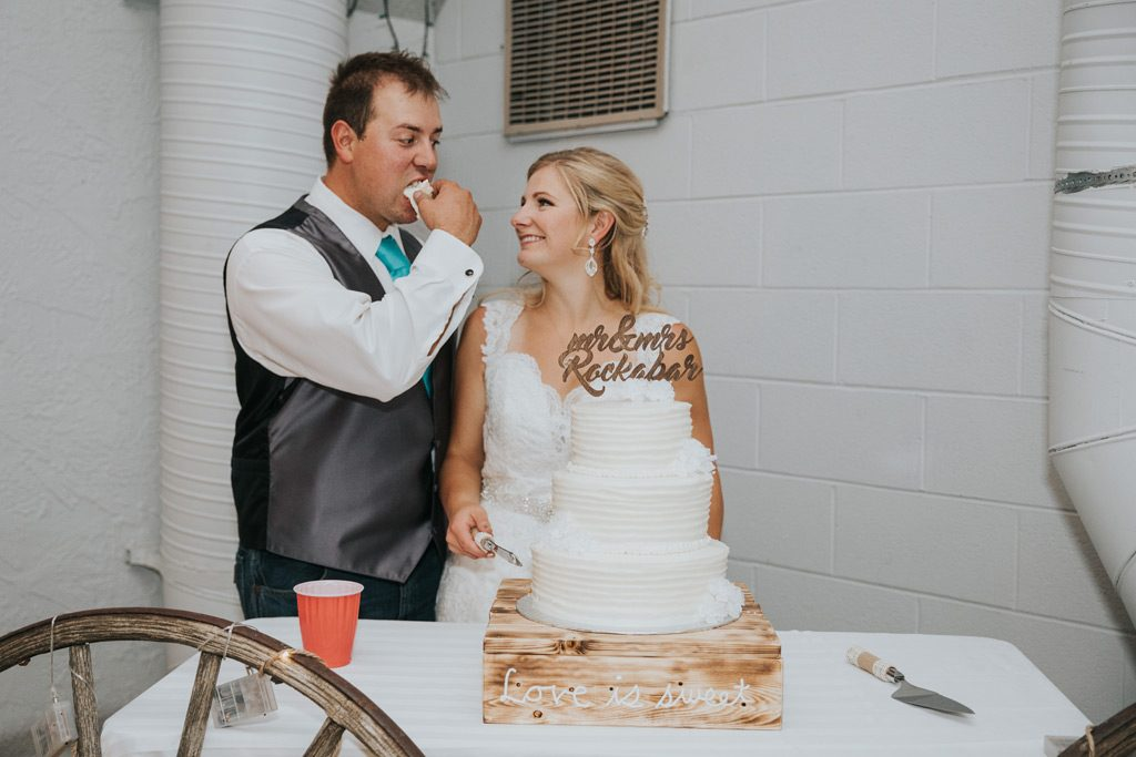 bride laughs as groom feeds cake to himself wedding reception