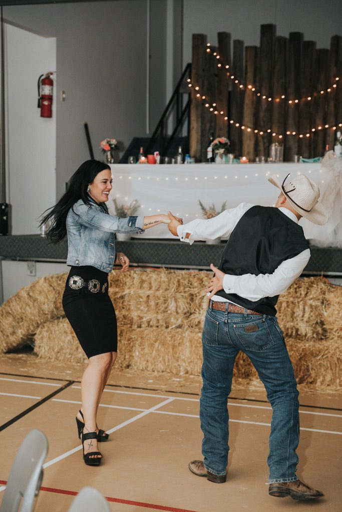 groomsman dances with guest twirling two stepping country wedding reception