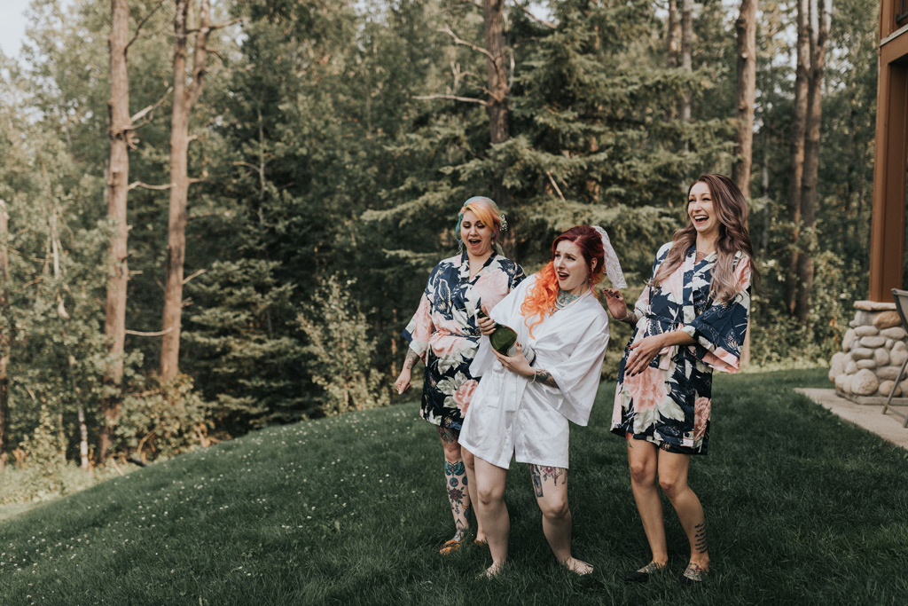 bride with bridesmaids popping champagne