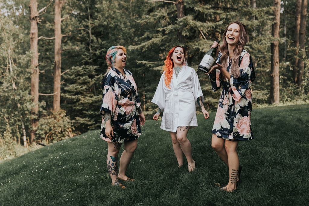 bridal party laughing drinking champagne from bottle