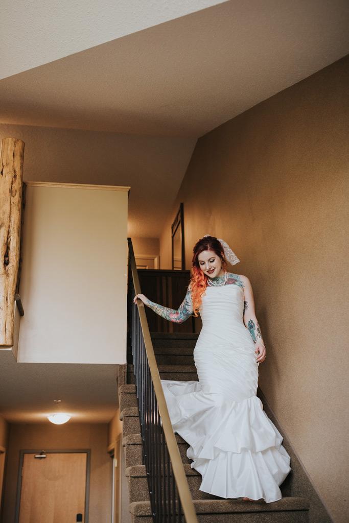 bride walks down the stairs in her dress elkwater lake lodge