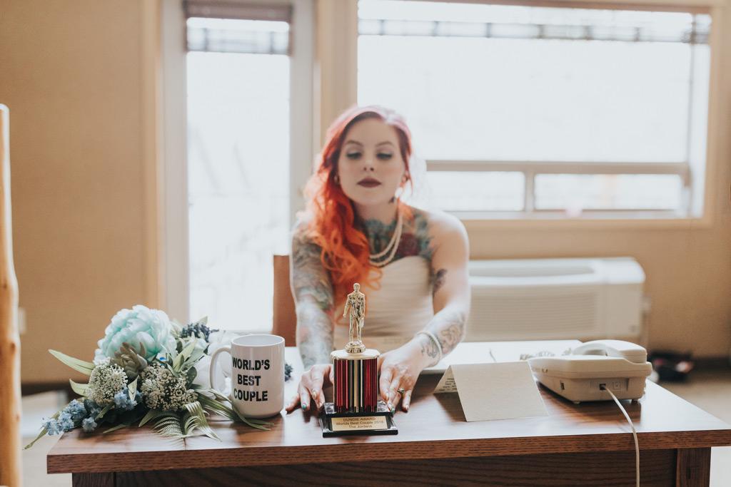 bride arranges trophy on desk The Office wedding