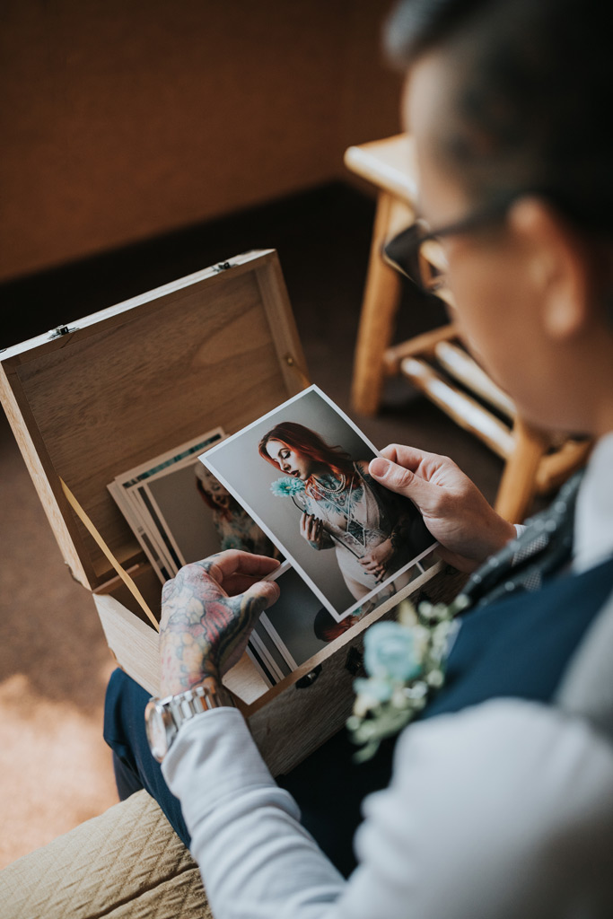 groom looking at bridal boudoir photos
