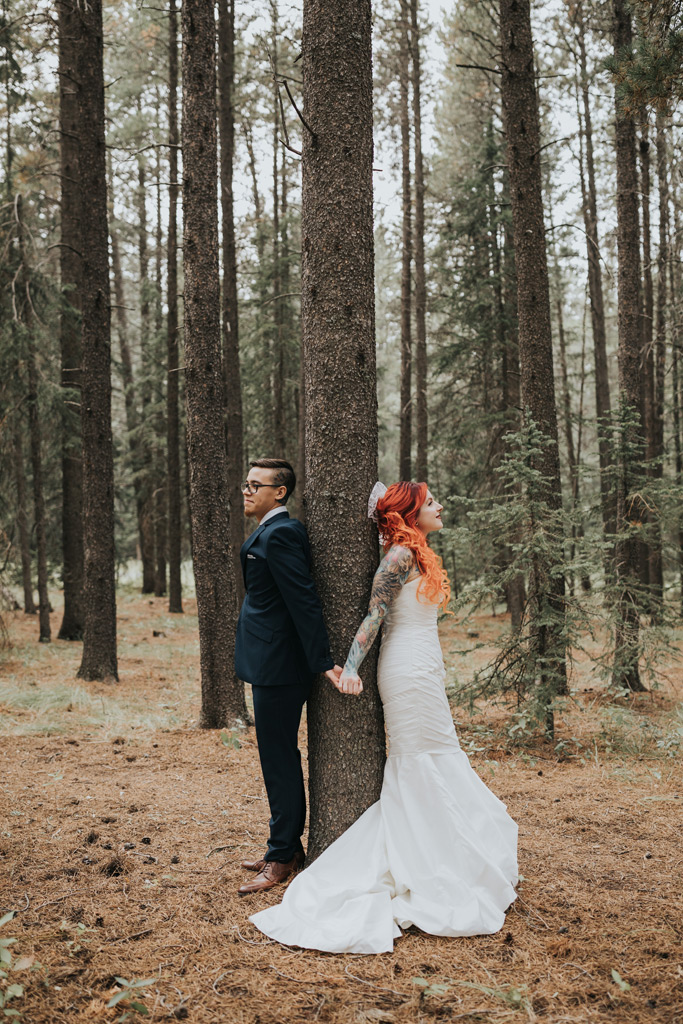 bride and groom hold hands back to back elkwater forest