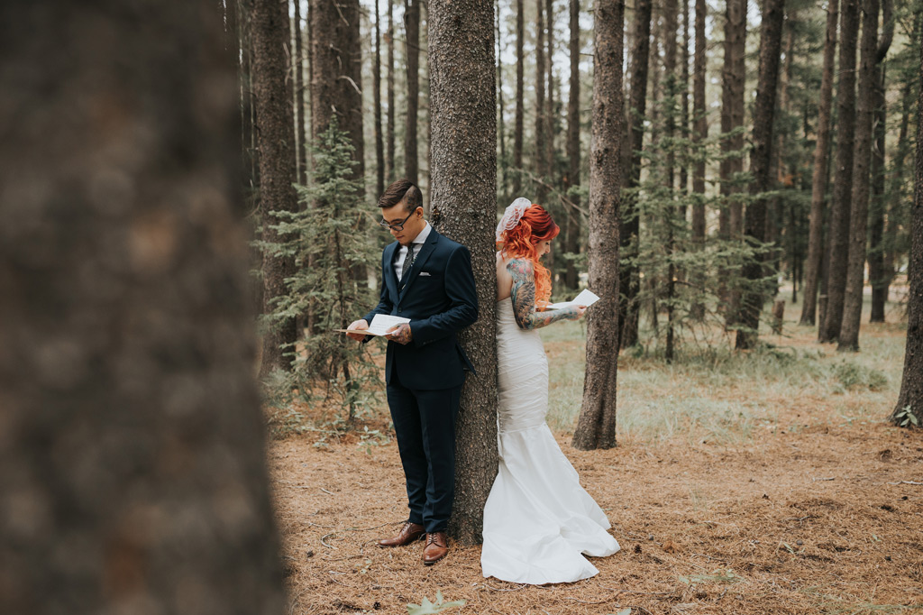 bride and groom stand back to back reading love letters