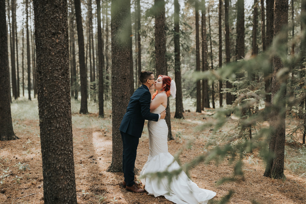 bride and groom kissing elkwater forest trees