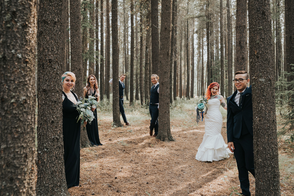 bridal party hiding behind trees forest