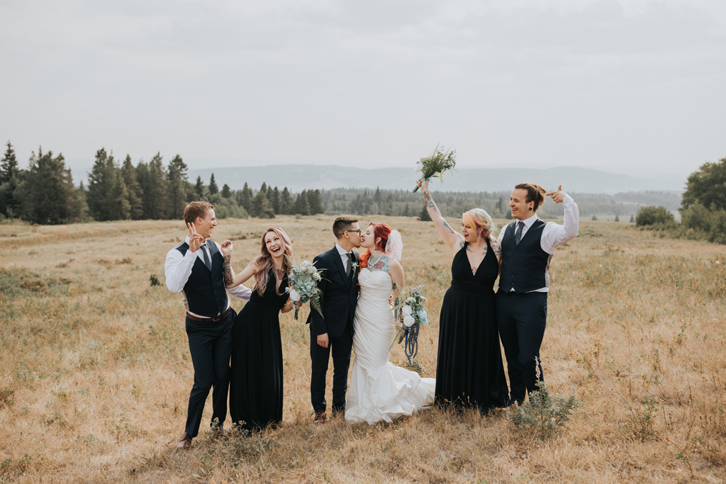 bridal party cheers as wedding couple kisses