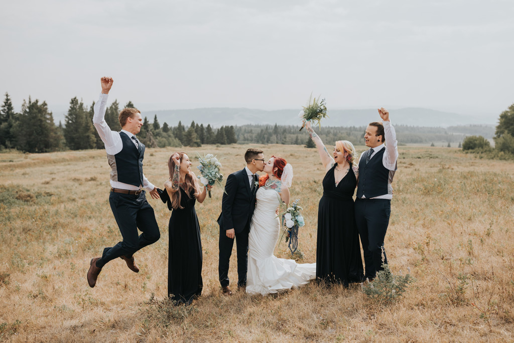 bridal party cheers bride and groom kiss