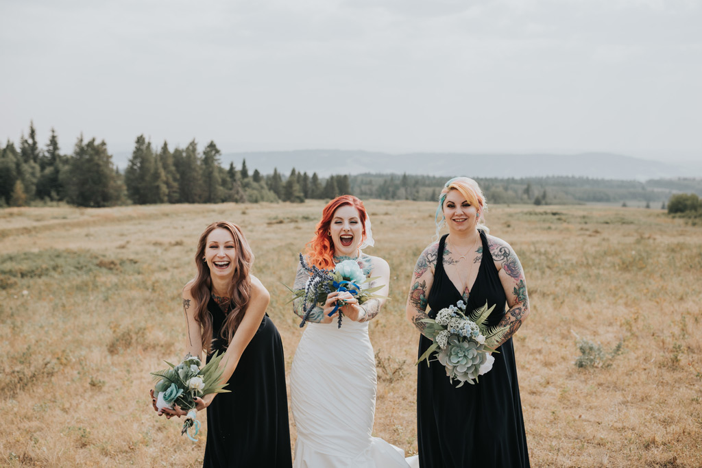 bridesmaids and brides laugh catching their bouquets