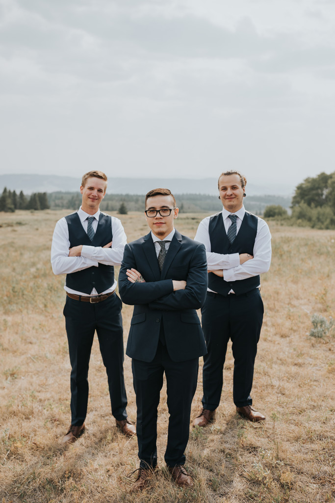 groomsmen stand arms folded