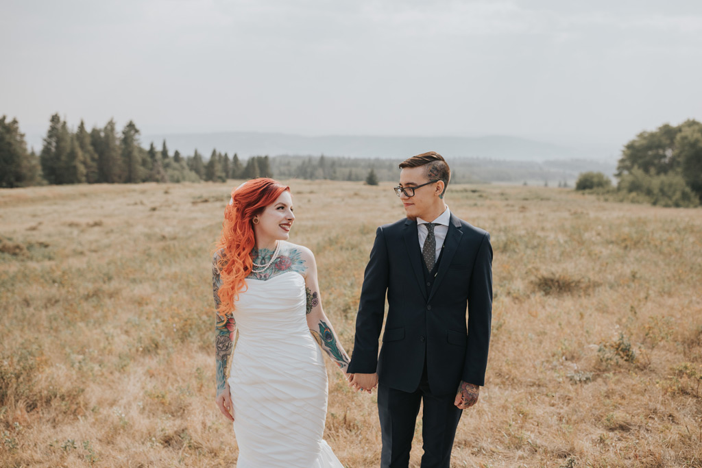 bride and groom hold hands head of mountain elkwater