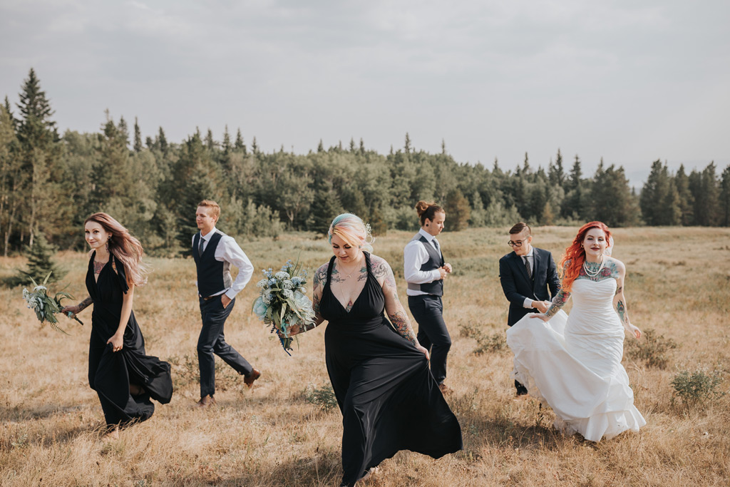 wedding party walks up hill head of mountain