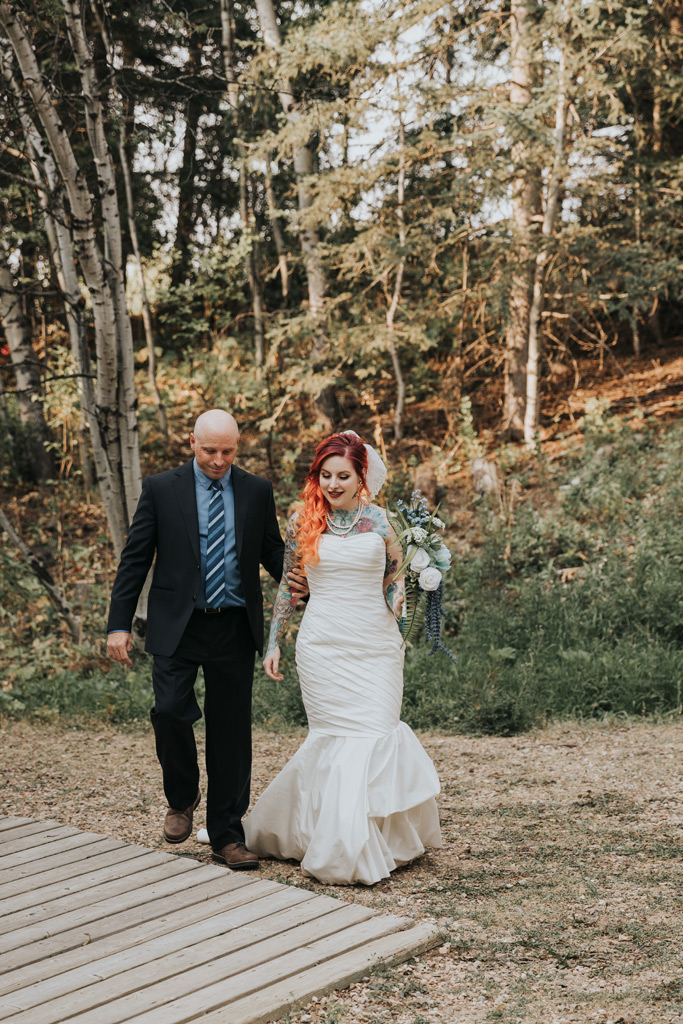 bride walks down aisle with her dad elkwater