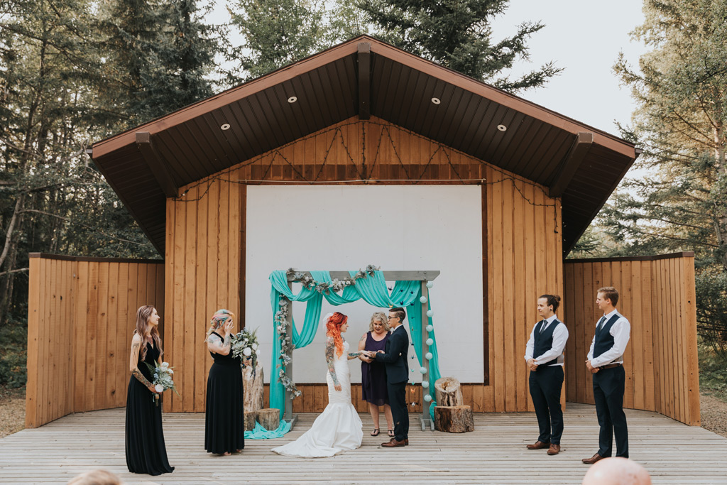 groom places ring on bride saying vows elkwater
