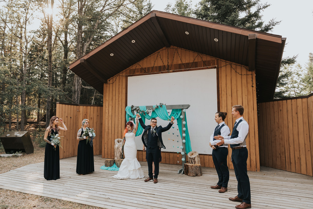 bride and groom raise arms after wedding ceremony