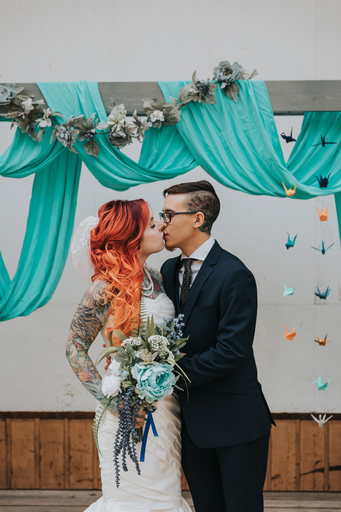 bride and groom kiss under colourful arch cranes