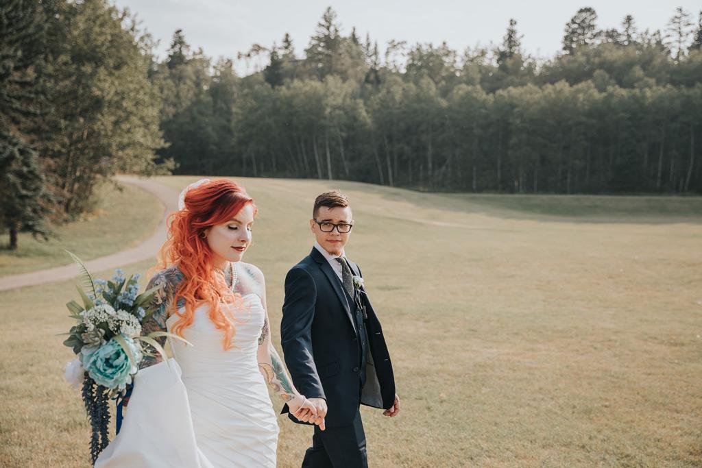 bride and groom walk holding hands