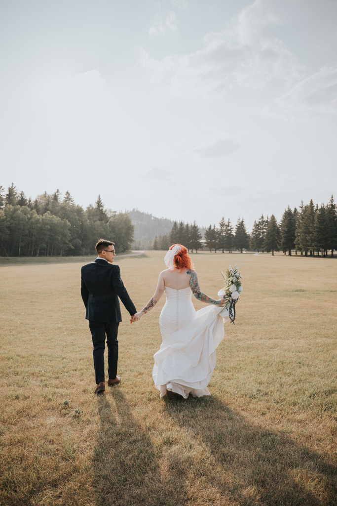 groom looks at bride walking into sunset