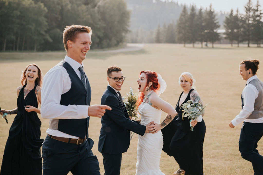 bridal party runs around bride and groom laughing