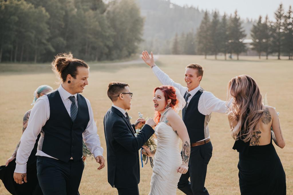 bridal party runs around bride and groom cheering