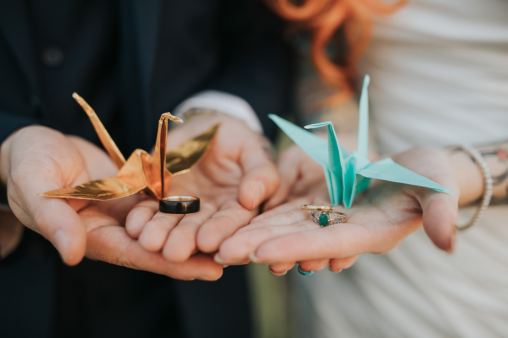wedding couple holds rings with cranes
