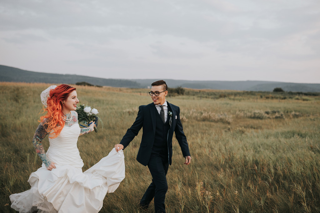 groom holds brides dress as they run through field