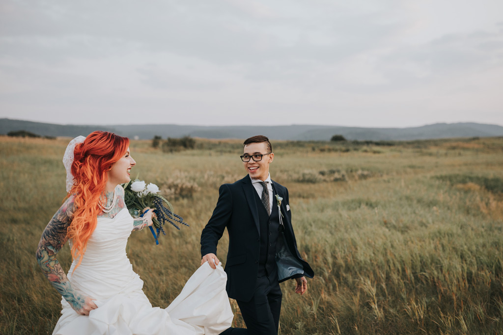 groom and bride laugh running through field