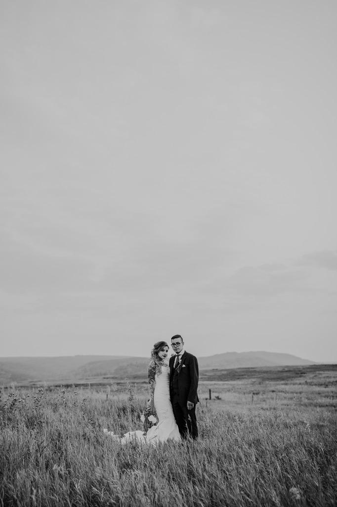 bride and groom pose in elkwater field