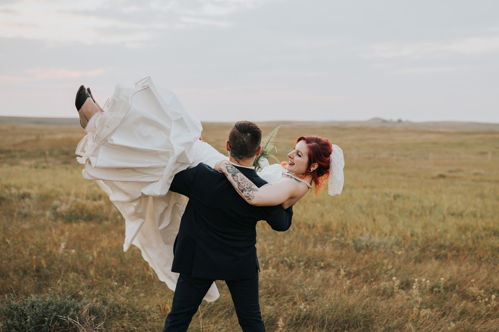 groom swoops up bride to carry her