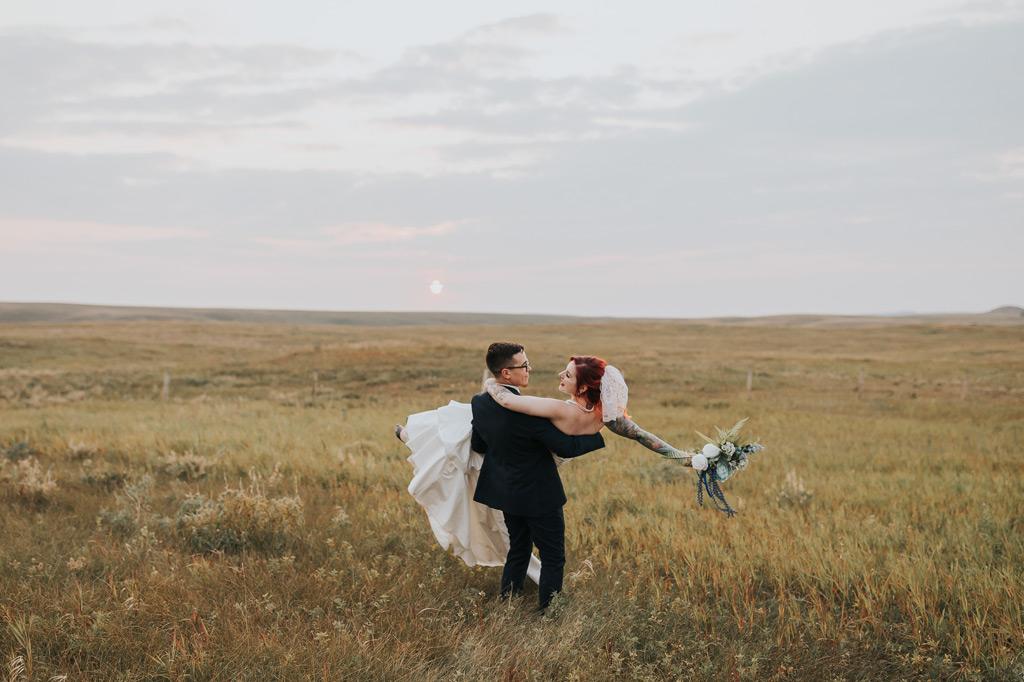 groom twirls bride around in field at sunset