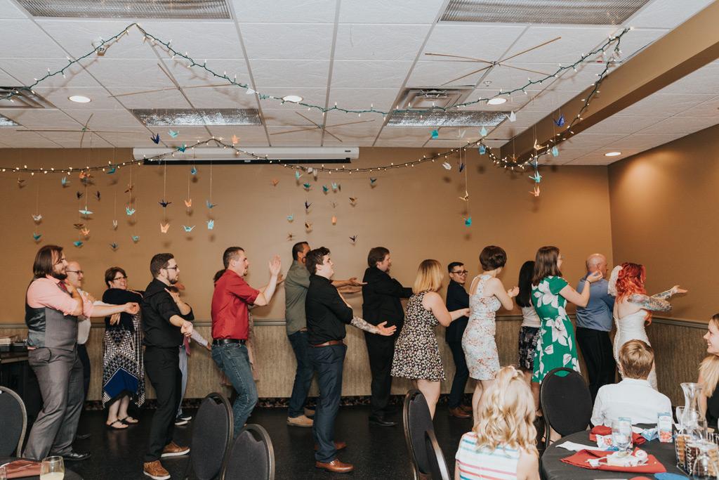 group dances macarena at wedding reception